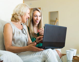 Woman learnig to use laptop from girl