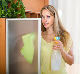 Blonde woman dusting glass