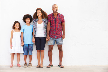 Family Standing Outdoors Against White Wall
