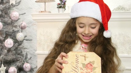 Little cute girl opening Christmas gift box