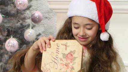 Little cute girl opening Christmas gift box