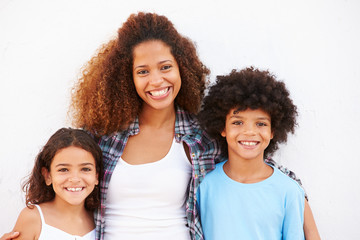 Mother And Children Standing Outdoors Against White Wall