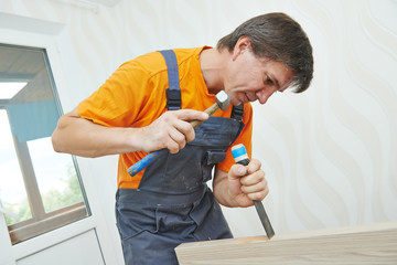 Carpenter works with hummer and chisel