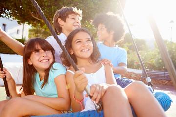Group Of Children Having Fun On Swing In Playground