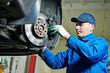 auto mechanic at car suspension repairing - 74398303