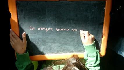 Niño escribiendo en pizarra