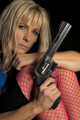 Woman in pink fishnet stockings hold gun look very serious