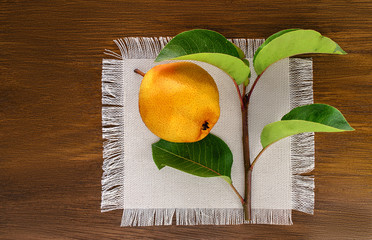 Ripe yellow pear with green leaves on a linen napkin