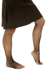 Woman legs in skirt and black fishnet stockings side