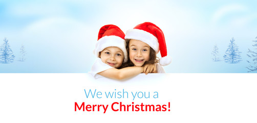 Happy little kids in Santa hat peeking from behind blank sign
