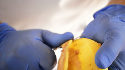 Hands of professional chef peeling potatoes with knife