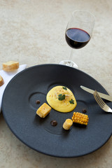 Egg with corn and polenta, glass of red wine