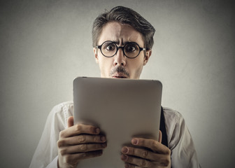 Surprised man reading something on a tablet