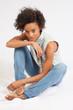 Black woman sitting looking thoughtful,