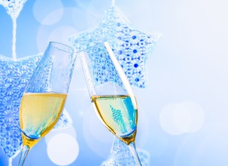 champagne flutes on blue christmas lights decoration background