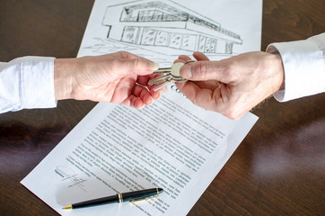 Estate agent giving house keys to customer