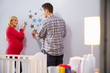 Couple With Pregnant Wife Adding Decorations To Nursery