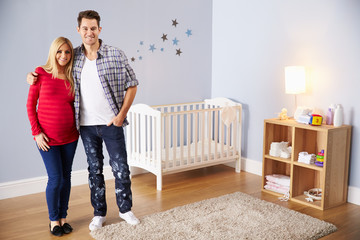 Couple With Pregnant Wife In Newly Decorated Nursery