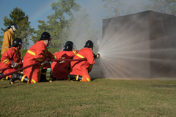 fireman watering against fire on training