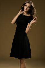Portrait of beautiful blonde woman in black dress. Fashion photo