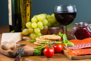 oat crackers and parma cheese with red wine on table