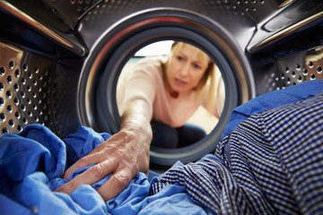 Woman Doing Laundry Reaching Inside Washing Machine
