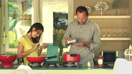 couple cooking, adding seasoning in kitchen