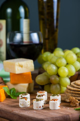 selection of soft cheese with fruits, spices and meat on board