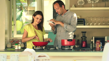 couple taking photo of food during cooking meal in kitchen
