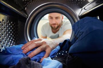 Man Doing Laundry Reaching Inside Washing Machine