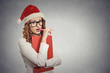 woman with christmas hat thinking of gift ideas grey background