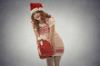 santa helper girl carrying big red christmas sack full of gifts