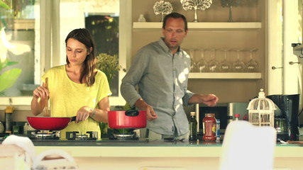 Young couple cooking spaghetti in kitchen at home