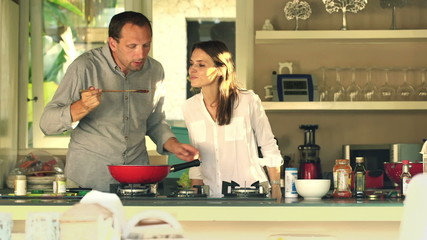Happy couple cooking and tasting prepared sauce in kitchen