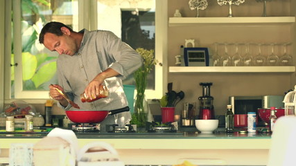 Handsome man cooking and pouring sauce in kitchen