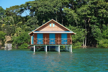 Bungalow over water with tropical vegetation
