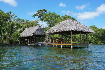 Thatched tropical hut and boathouse over the sea