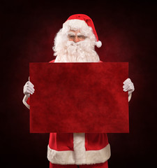 Santa Claus holding a red sign