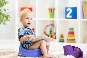 toddler sitting on chamber pot playing tablet pc