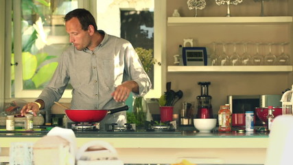 man tasting sauce and adding seasoning in kitchen