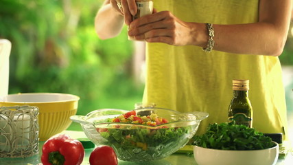 Woman hands adding seasoning to salad in kitchen