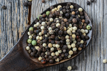 black ,white, green, brown peppercorns on rustic wooden table
