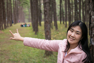 Girl with a smail in pine plantation