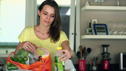 Young, pretty woman unpack groceries in kitchen at home