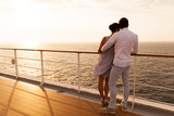 young couple hugging at sunset on cruise ship