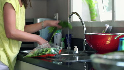 Woman hands washing spinach in kitchen at home