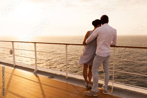 Leinwanddruck Bild young couple hugging at sunset on cruise ship