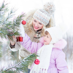 Happy mother and child decorating christmas tree outdoor