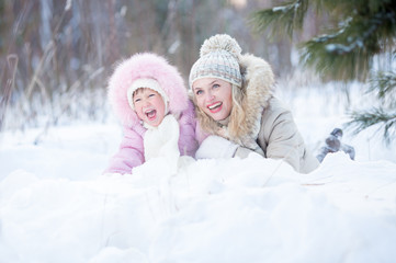 Happy mother and kid lying in snow outdoor