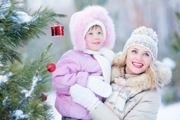 Happy mother and child with decorated christmas tree outdoor